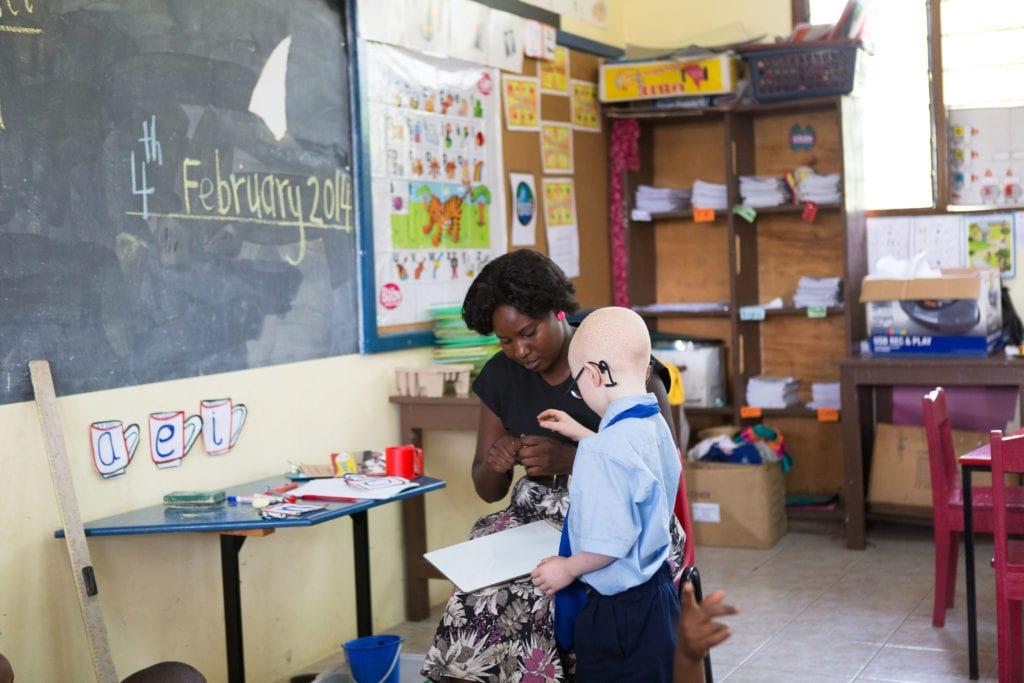 Lower Primary teacher Anna Nnko helping Sebastian in class