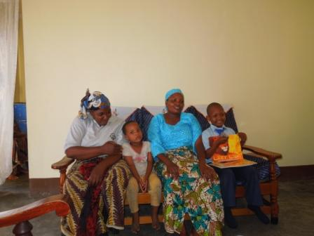 Lebahati proudly holding his books - he is with his family, in their home
