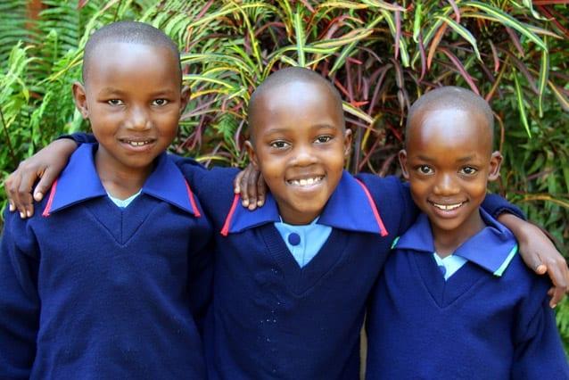 Happy environment: Asha (middle) has enjoyed making new friends like Rogathe (left) and Fatuma.