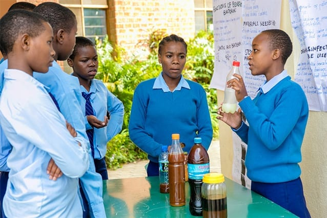 Sesilia (Form 3) explains her organic disinfectant project to fellow students at St Jude's Science Day.