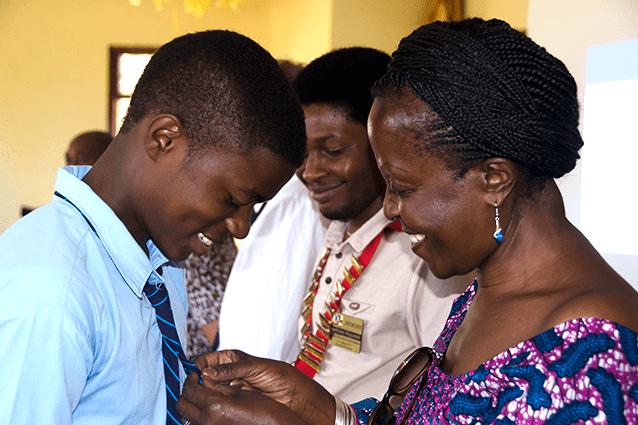 All smiles: Form 4 student Edgar appreciatively accepts a club pin from Arusha Mt Meru club President Anna Rweyemamu.