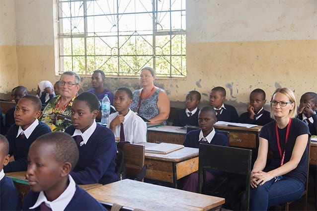 Bringing it home: Wens (pictured back, left) accompanies visitors to local government schools.